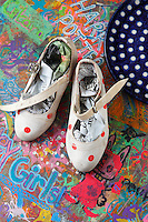 A pair of vintage flamenco shoes is displayed beside a polka-dot plate on the dining table, customised in felt pen