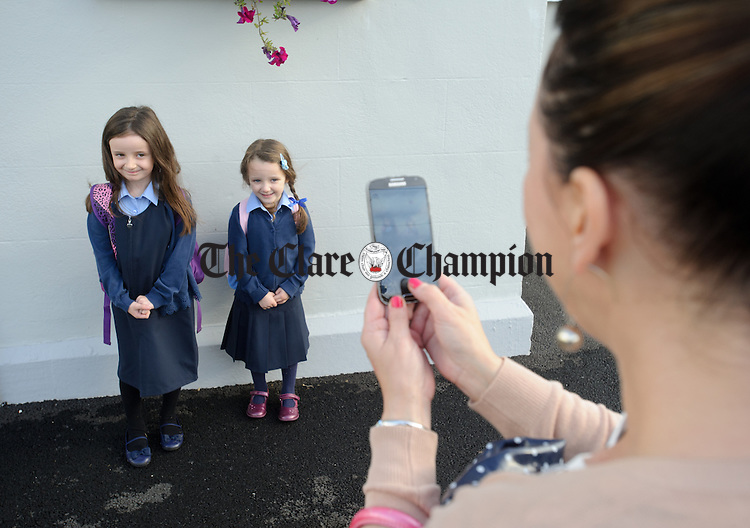 Jennifer Rooney takes pictures of her daughter Lydia, a senior infant, and her junior infant daughter Iris on their first  in school at Boston NS. Photograph by John Kelly.