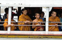 Monks share a ride on the Chao Phraya River in Bangkok with commuters and tourists.
