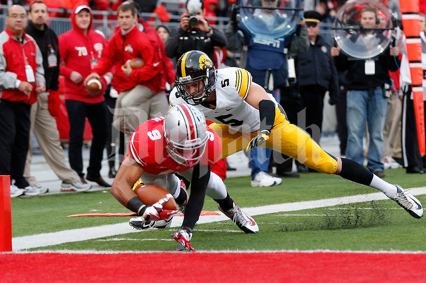 Ohio State Buckeyes wide receiver Devin Smith (9) dives for a touchdown under pressure from Iowa Hawkeyes defensive back Tanner Miller (5) in the third quarter of the NCAA football game between the Ohio State Buckeyes and the Iowa Hawkeyes at Ohio Stadium in Columbus, Saturday afternoon, October 19, 2013. The Ohio State Buckeyes defeated the Iowa Hawkeyes 34 - 24.  (The Columbus Dispatch / Eamon Queeney)