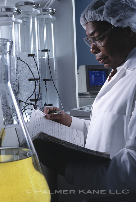 Black scientist checking notes in lab