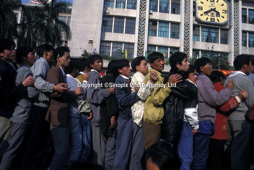 Migrant workers queue for train tickets in Guangzhou, Guangdong, China.  China's transport system is becomming increasingly stretched as more and more people travel..12 Mar 2004