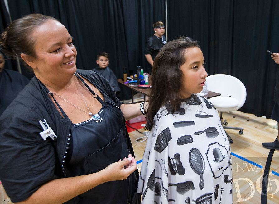 NWA Democrat-Gazette/BEN GOFF @NWABENGOFF<br /> Denise Myers, owner of DeSigner Barber & Stylist School, finishes a haircut for Angelina Virto, 10, of Fayetteville Saturday, Aug. 10, 2019, during the Northwest Arkansas Community Back to School Extravaganza at the Yvonne Richardson Community Center in Fayetteville. Four area churches; St. James Missionary Baptist Church, Good Shepherd Lutheran Church, Agape Ministries and New Heights, partnered to put on the event. Community partners provided free vision and dental screenings, haircuts, blood pressure checks for parents and backpacks full of school supplies. Myers and her students provided free haircuts to children at the event.