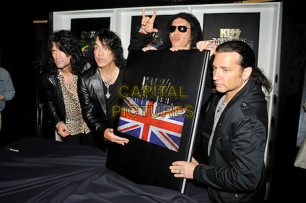 KISS - Tommy Thayer, Paul Stanley, Gene Simmons and Eric Singer .attending the 'KISS Monster' book launch, The Arts Club, London, England. .3rd July 2012.half length black suit jacket sunglasses shades  white print scarf band group leopard large giant oversized book hand devil hand sign gesture mouth open.CAP/MAR.© Martin Harris/Capital Pictures.