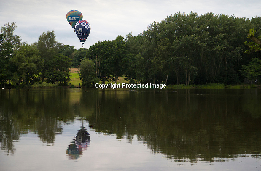 07/06/16<br /> <br /> The balloons are reflected in Allestree Park fishing lake.<br /> <br /> After weeks of rain the Nottingham and Derby Hot Air Balloon Club finally get to launch their three hot air balloons from Allestree Park, Derby.