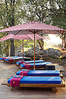 Sun loungers and parasols on a terrace at the Singita Pamushana Lodge, Malilongwe Trust, Zimbabwe
