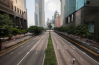 A man takes a photo on normally busy Gloucester Road, a main thoroughfare through Hong Kong's busy Wan Chai district, appears strangely quiet on day three of the mass civil disobedience campaign Occupy Central, Hong Kong, China, 30 September 2014.