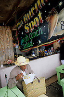 Iles Bahamas / New Providence et Paradise Island / Nassau: Dans un petit restaurant de rue du Marché de Potter's Cay sous le pont de Paradise Island - une cliente mange une salade de conque Conch Salad spécialité emblématique de la cuisine bahamienne