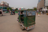 Daytime landscape view of a man in a tricycle taxi Shao Hua Lu in front of the Bozhou Train Station in Bozhou in Qiáochéng Qū in Anhui Province.  © LAN