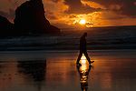 A walk on the beach at sunset on the Oregon Coast. In the background is a part of Haystack Rock.