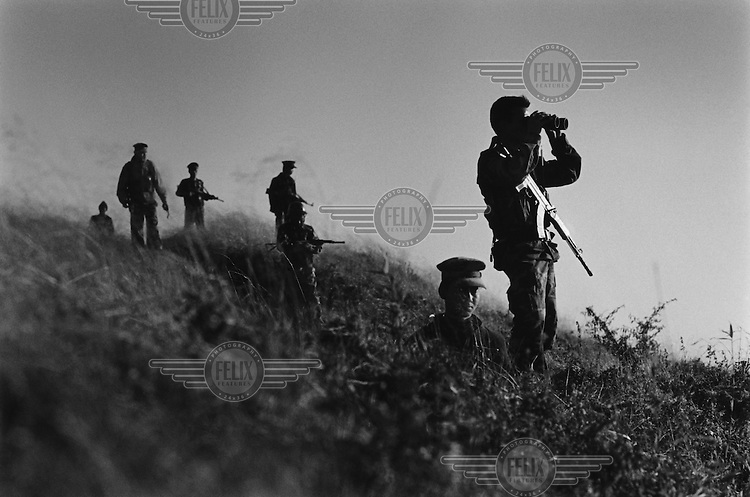 Soldiers of the Kachin Independence Army (KIA) look over Burmese Army positions on the frontline at Bum Sen post, 7,500 feet above sea-level.