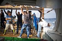 Giornalisti su una barca di pescatori a largo delle coste di Lampedusa.