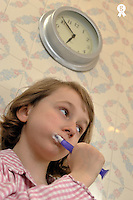 Girl (8-9) brushing her teeth under clock (Licence this image exclusively with Getty: http://www.gettyimages.com/detail/87125933 )