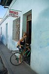 Woman parking her bicycle inside a barbershop, Santa Clara, Villa Clara, Cuba.