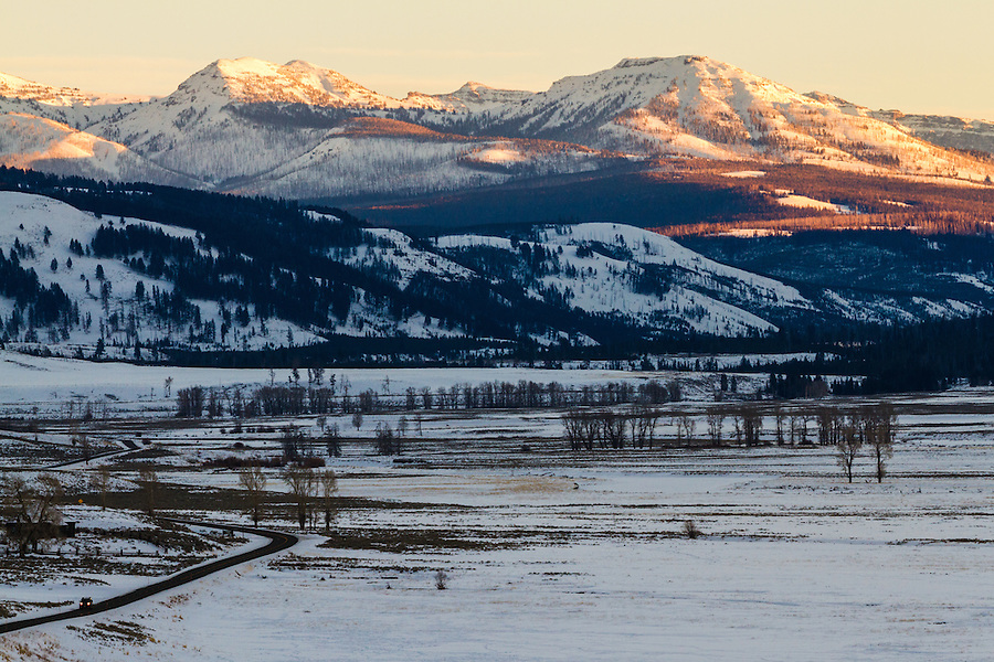 Warm sidelighting from the sun illuminates the surrounding hills above the Lamar Valley in Yellowstone National Park, Wyoming.