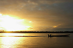 The Marowijne River, Suriname.  Maroon man in dugout with Rastafarian flag heads up river at sunset.