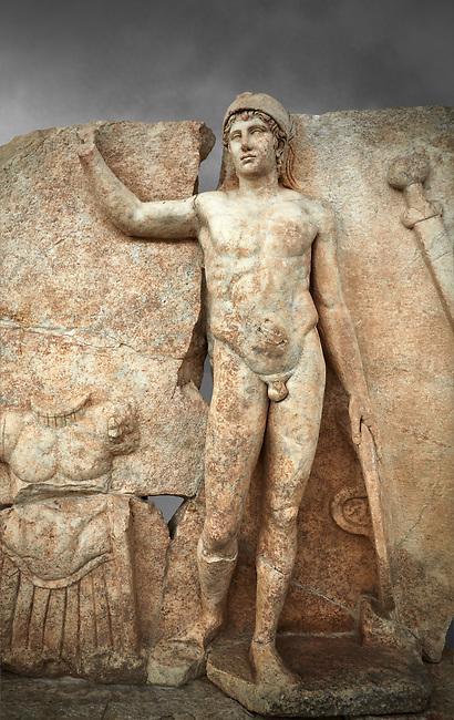 Close up of a Roman Sebasteion relief  sculpture of Ares, Aphrodisias Museum, Aphrodisias, Turkey.  Against a grey background.<br /> <br /> The nude and classically7 styled young god wears only a helmet and holds a spear (missing) in one hand and a shield in the other. At the left stands cuirass, and at the upper right corner hangs his sword. Ares was a god of war and was not later defaced by Christians probably because he so closely resembles a young emperor.