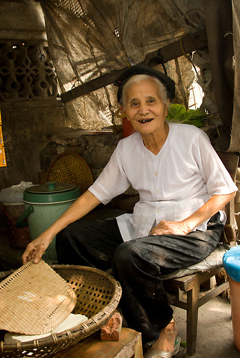 An older woman proudly displaying her rice curd in the small village of Tho Ha just outside of Hanoi, Vietnam. You can also see her teeth are stained from the chewing of betel nut.