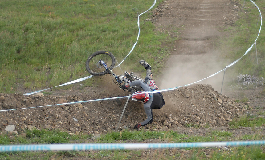 A downhill mountain bike racer crashes during practice during a downhill race at Sol Vista in Colorado