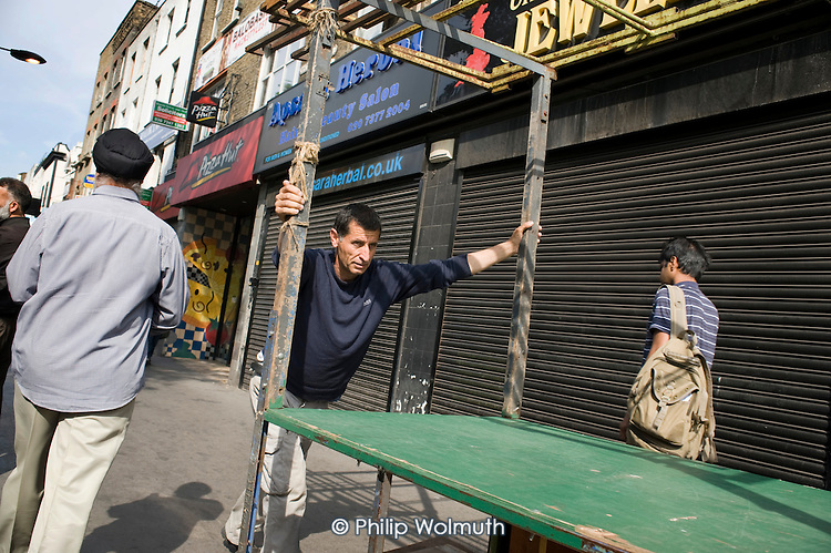 A market trader wheels out his stall at the beginning of the day, Whitechapel, London.