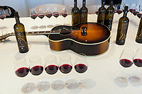 Switzerland. Canton Ticino. Cagiallo. Merlot wine testing for the new Magnificents' 17. On the table, among wine bottles and glasses, a guitar Gibson Super Jumbo, SJ-200, belonging to Leo Leoni. The Swiss rock band Gotthard is associated with winemakers Valentina Andrei (Merlot Ivresse from Valais) and Sacha Pelossi (Merlot from Ticino) to create the new assemblage (50-50 from both winemakers) for a unique vintage bottle: Magnificents' 17. Gotthard is a Swiss hard rock band founded in Lugano by Steve Lee and Leo Leoni. Their last eleven albums have all reached number 1 in the Swiss album charts, making them one of the most successful Swiss acts ever. With 2 million albums sold, they managed to get multi-platinum awards in different parts of the world. Cagiallo is a village and and is part of the Capriasca municipality. 25.03.2019 © 2019 Didier Ruef