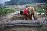 In preparation for All Souls Day, Rufina Soren repairs the grave of her father in the Christian cemetery in Suihari in northern Bangladesh.