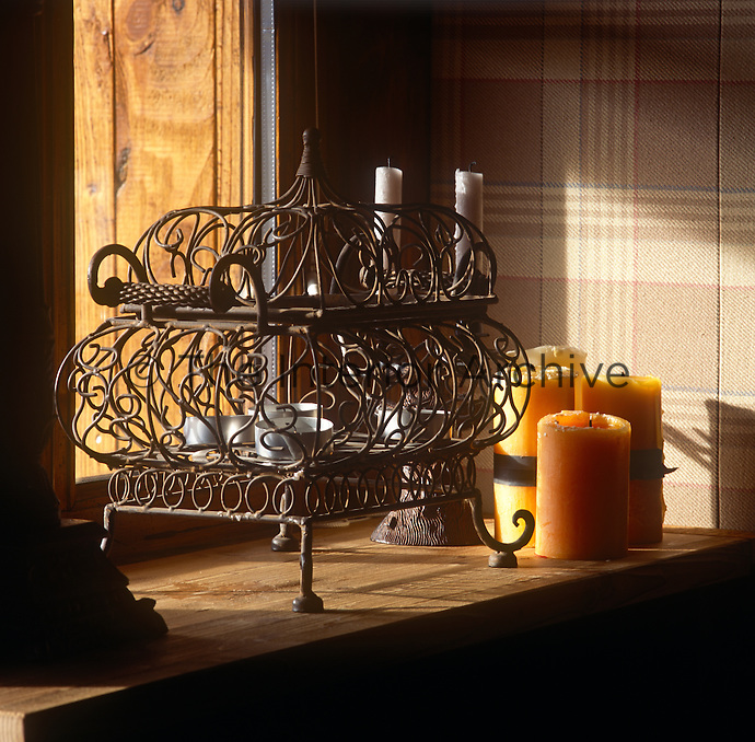 A metalwork cage with tealights inside stands on a wooden chest.