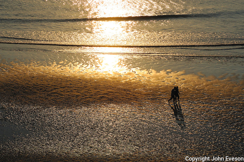 Two people walking over a beach at sunset, Perranporth, Cornwall.