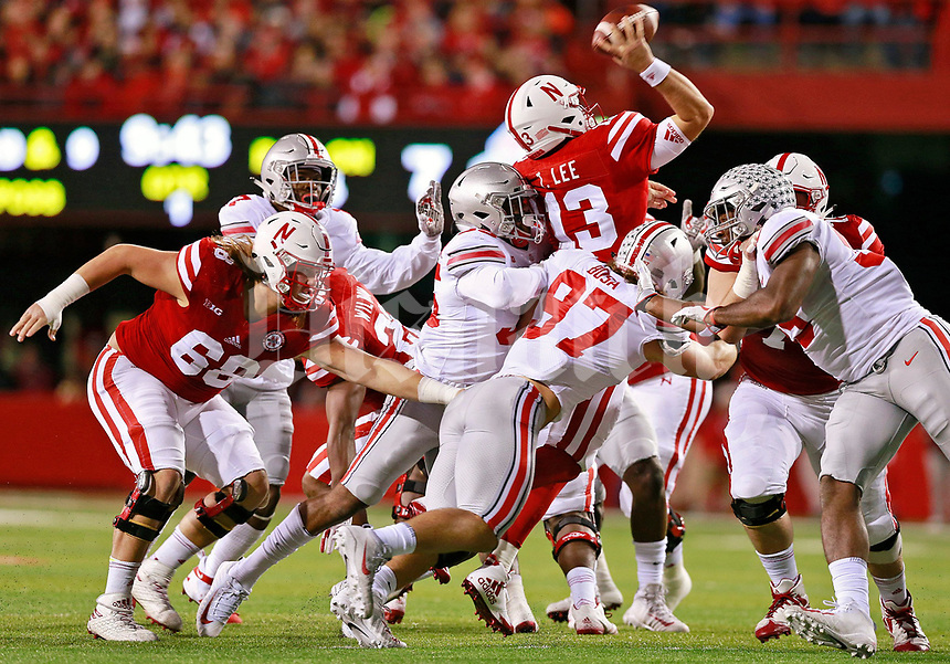 Nebraska Cornhuskers quarterback Tanner Lee (13)is tackled by Ohio State Buckeyes linebacker Chris Worley (35) and lineman Nick Bosa (97) during the first quarter of Saturday's NCAA Division I football game at Memorial Stadium in Lincoln on October 14, 2017. Ohio State won the game 56-14. [Barbara J. Perenic/Dispatch]