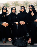 OMAN, Barr Al Jissa Resort and Spa, Muslim women sitting side by side in traditional clothing.