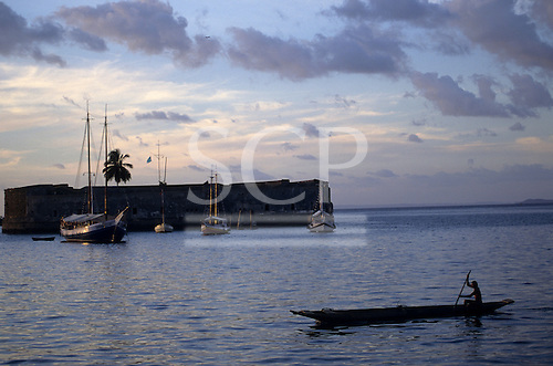 Salvador, Bahia, Brazil. A man paddling a canoe past the old fort, Sao Marcelo, at dusk with single palm tree and sailing boats