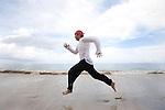A man in a white shirt and red bandana runs along the beach in Koh Lanta, Thailand.