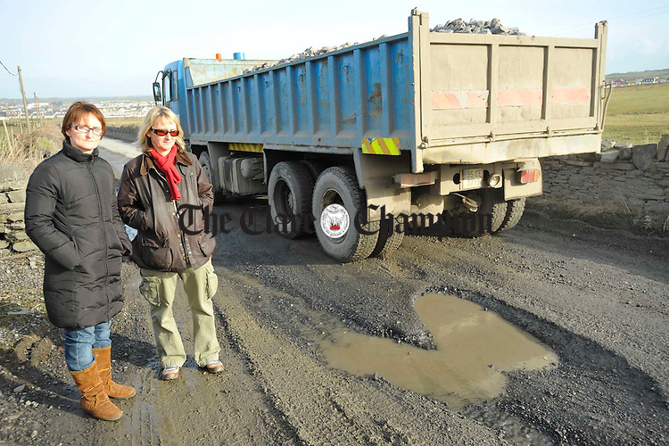 Members of the local business community and residents Rosarie and Elaine Haugh show some of the damage done by passing trucks laden with gravel and stone, near their home place at Dunlicky road, Kilkee. Photograph by John Kelly.