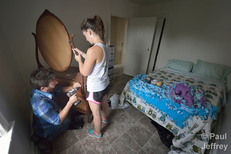 Josh Digrugilliers and Emilie MacDonald assemble a dresser in the bedroom of an apartment in Lancaster, Pennsylvania. They are furnishing what will become home for a refugee family about to arrive in the United States. The two work for Church World Service, which resettles refugees in Pennsylvania and other locations in the United States. <br /> <br /> Photo by Paul Jeffrey for Church World Service.