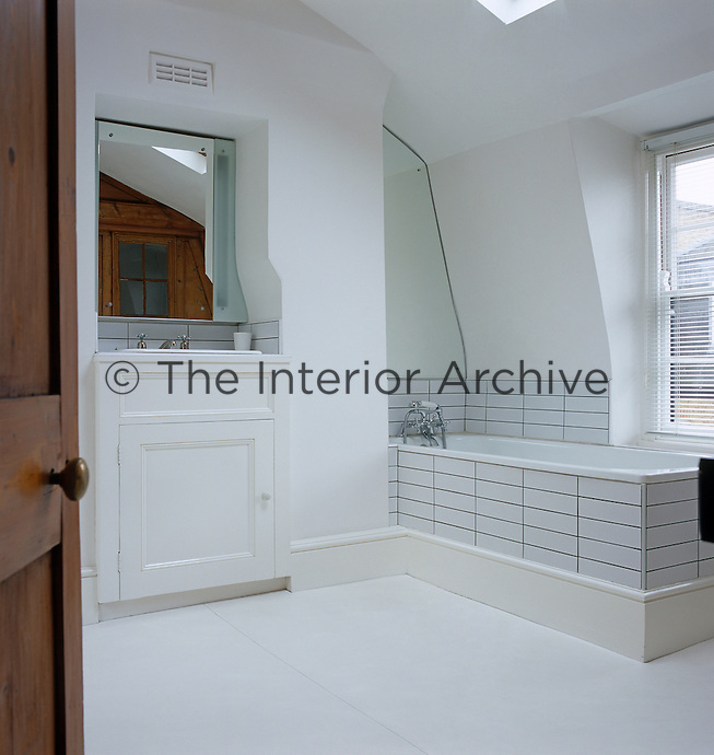 Gloss and matt paint finishes on floor and walls in this bathroom enliven a plain colour scheme with reflections and variation