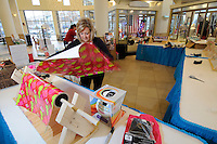 NWA Media/ J.T. Wampler - Brenda Majors wraps Christmas presents Monday Dec. 22, 2014 at the food pavilion at Pinnacle Hills Promenade. Presents will be wrapped for until Christmas Eve at 3p.m. Donations are accepted for the wrapping service with proceeds benefitting the Camp Alliance Silver Star Gift Program.