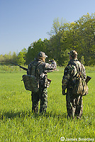 Two men in camouflage hunting for wild turkey