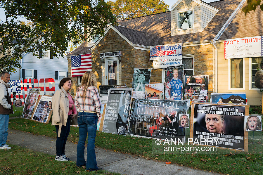 Bellmore, New York, USA. November 2, 2016. EILEEN FUSCALDO, seen from behind at right, is talking with neighbors and others in front of her home Halloween display, with signs against Democratic presidential candidate Hillary Clinton, and in support of the Republican  Donald Trump. They're in front of a mock-up photo of Clinton in jail.