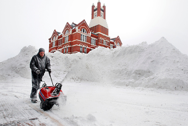 Justin Hunolt clears snow with a snow blower next to a 20-foot pile of snow in front of the Mahaska County Courthouse in downtown Oskaloosa, Iowa Tuesday morning February 2, 2011.  The huge piles of snow, many locals saying the largest they've ever seen,  dotted the town in each intersection, waiting for removal.