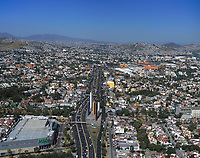 aerial photograph of Ciudad Satelite, Naucalpan, State of Mexico north of Mexico City, Mexico with the Mega Supermarket and Torres de Satelite landmark in the foreground viewed down the highway toward Queretaro