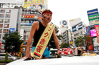 "Mac Akasaka campaigning in Shibuya. real name, Makoto Tonami, he is chairman of the ""Smile Therapy Association Foundation."" and is the sole candidate of the ""Japan Smile Party."" Akasaka's policies call for the dissolution of Japan's Self Defense Forces and a lowering of the voting age. He believes these measures will help bring about an increase in happiness in Japan's population. Shibuya, Tokyo, Japan June 26th 2010 Makoto Tonami, known as Mac Akasaka campaigning for election in Shibuya. He is chairman of the ""Smile Therapy Association Foundation."" and the sole candidate of the ""Japan Smile Party."" Akasaka's policies call for the dissolution of Japan's Self Defense Forces and a lowering of the voting age. He believes these measures will help bring about an increase in happiness in Japan's population. Shibuya, Tokyo, Japan June 26th 2010"