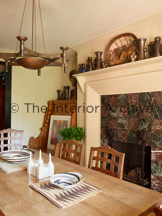 The Arts and Craft style table in the kitchen was designed by Anthony Collett and open shelving above the fireplace displays further examples from his ceramic collection