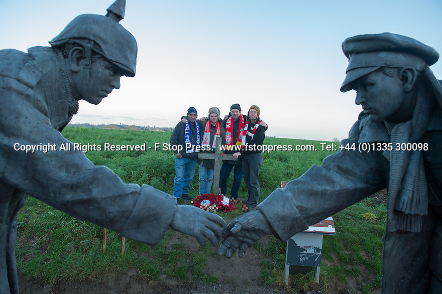 """25/12/14<br /> <br /> Football fans from around the world pay their respects by a sculpture depicting two WW1 soldiers playing football during the famous Christmas Day truce in the field near Messine, Belgium, close to where the match was played in Flanders, Belgium.<br /> <br /> The sculpture, made in England, arrived in Flanders on Christmas Eve, and was first displayed in the town centre before being taken to the spot where the match was played. <br /> <br /> Sculpted by Andy Edwards the work is entitled 'All Together Now', recalling the song by the band The Farm - which was inspired by the truce. <br /> <br /> Chris Butler said: """"Castle Fine Arts are proud to have cast a number of war memorials over the years. We are honoured to support this sculpture for peace. I believe it will touch the hearts of millions.""""<br /> <br /> <br /> """"It will be a symbol of peace and hope and a call for a renewed worldwide cessation of violence in honour of those brave boys who 'joined together and decided not to fight'"""".<br /> <br /> <br /> The statue depicts the meeting of a British and a German soldier over a football, deep in the mud between the lines on that first Christmas of the war. The soldiers appear to be shaking hands but  are not not quite touching, forming a space in which a visitor can insert their own hand to complete the union.  A chance for a moments reflection on how far we are from true peace and brotherhood and the part each of us has to play in that dream. We want the work to stand as both a celebration of this inspirational and heroic event and as symbol of hope and peace. <br /> <br /> The project was instigated some years ago, with the support of the Football Asscociation (FA), as football's contribution to the First World War commemorations. <br /> <br /> All Rights Reserved - F Stop Press. www.fstoppress.com. Tel: +44 (0)1335 300098"""