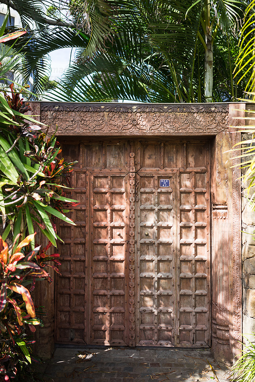A decorative wooden doorway beneath palm trees