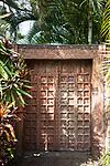 A decorative wooden doorway beneath palm trees