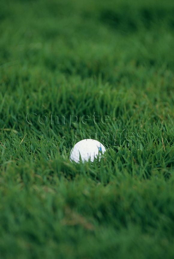 Close up of a golf ball in thick grass