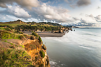 Sunset on coastline with Three Sisters rock formation and Tongaporutu River near Taranaki, New Plymouth, Taranaki Region, North Island, New Zealand, NZ