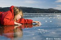 Happy young girl lying on the frozen lake ice