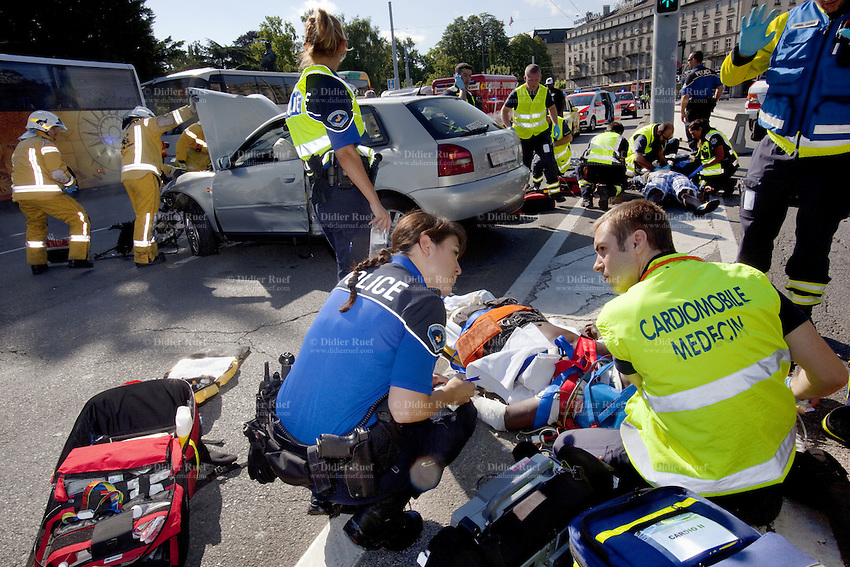 Switzerland. Geneva. A police officer talks to an emergency doctor after a car accident on the Mont-Blanc bridge. Two wounded men and a destroyed Audi A1. Firefighters and policemen at work. 7.07.12 © 2012 Didier Ruef..