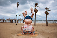 A sign calling people to stay home to reduce the spread of the new coronavirus is placed on a statue of the first Israeli Prime Minister David Ben Gurion at a beach in Tel Aviv, Israel, March 20, 2020. (AP Photo/Oded Balilty)